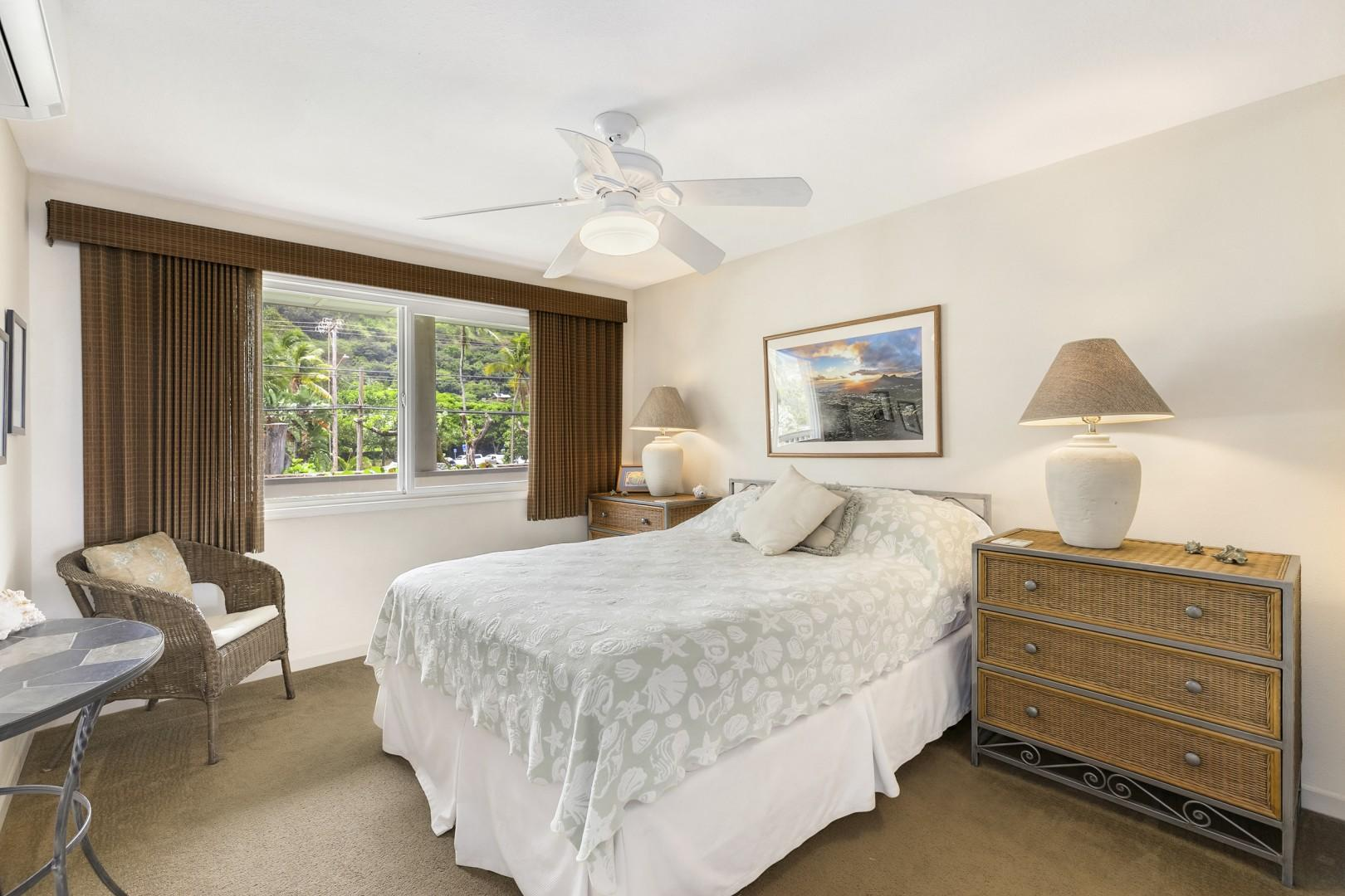 Guest bedroom with queen bed, ceiling fan, split AC, dresser, and closet.