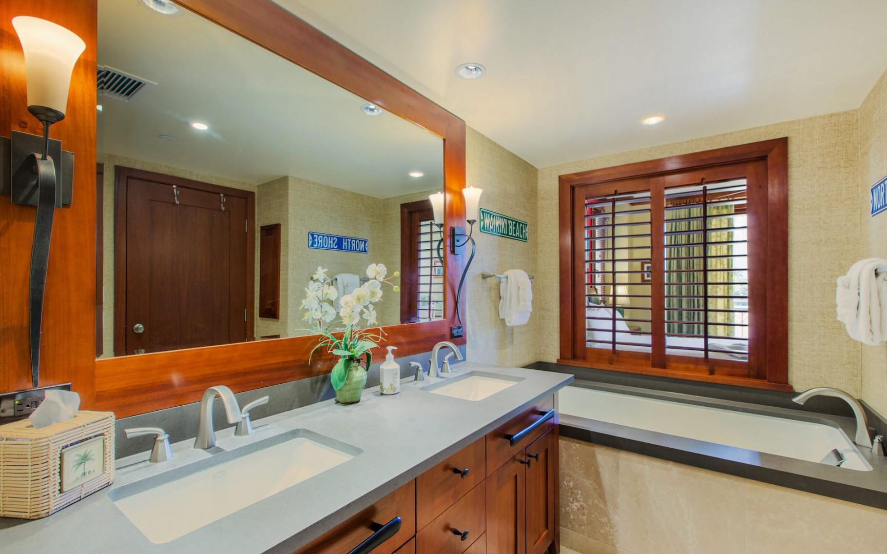 Master bathroom with deep soaking tub, separate tiled/glass shower, dual sinks, mahogany plantation shutters open/close between the bathroom and the bedroom. A starter supply of bath amenities and toilet paper is included.