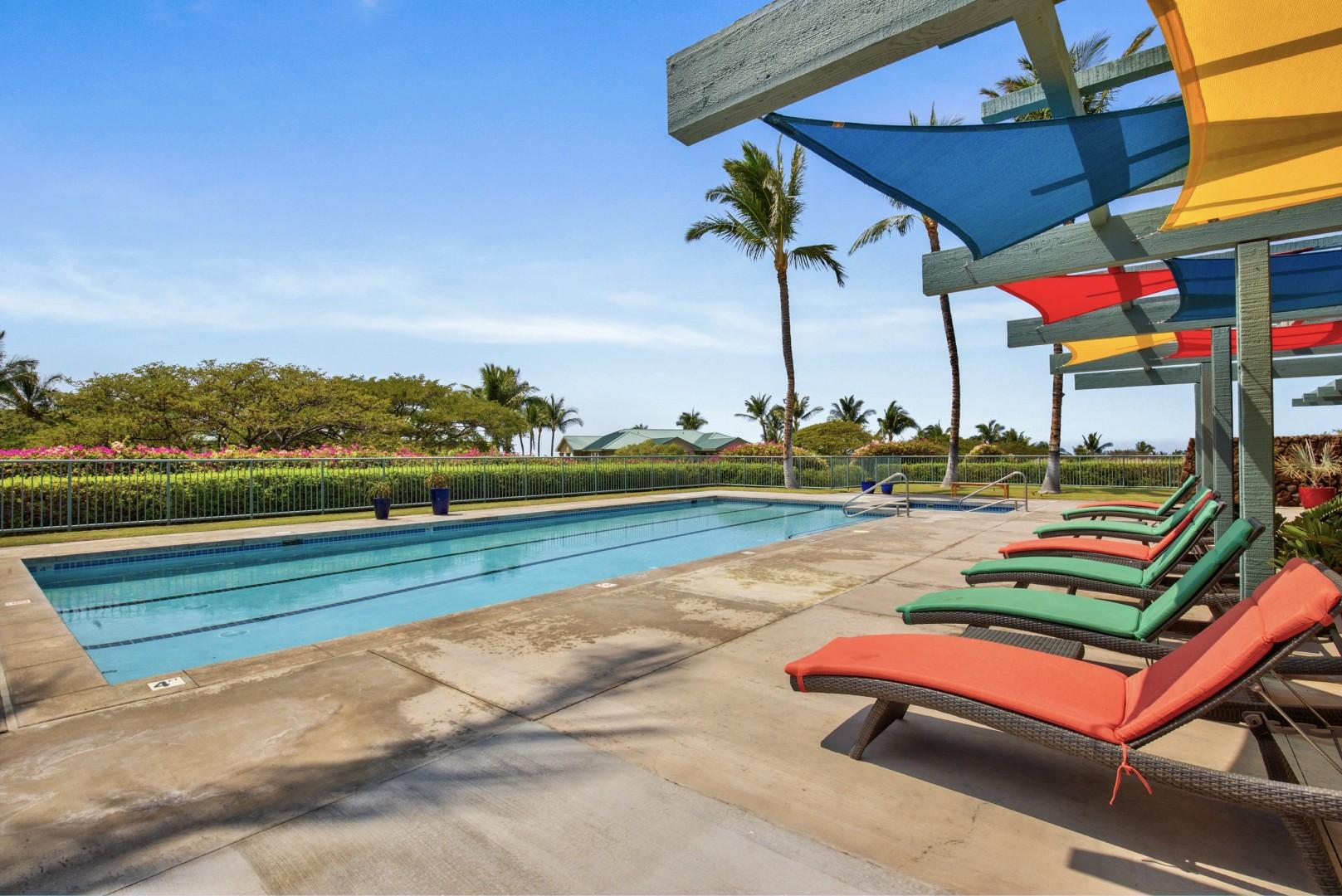 Alternate view of amenities center pool with colorful loungers and shade sails.