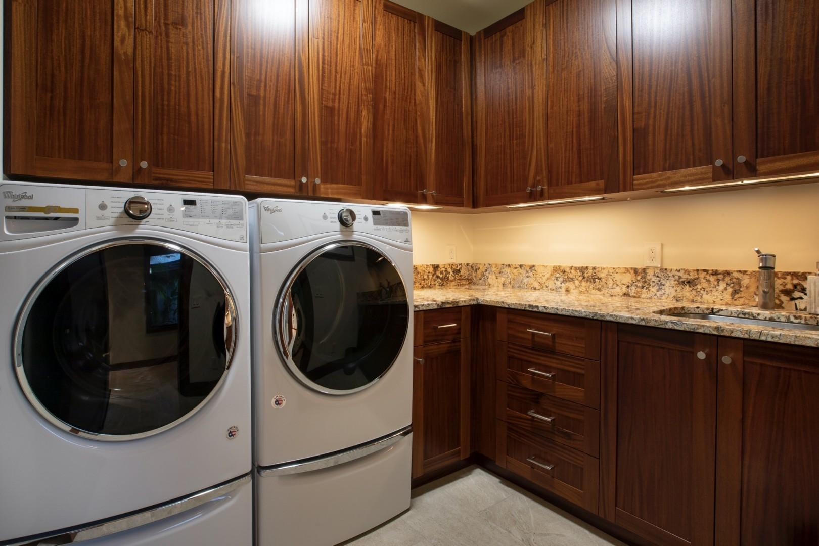 Dedicated laundry room with oversized Whirlpool washer and dryer, sink and ample counter prep space.