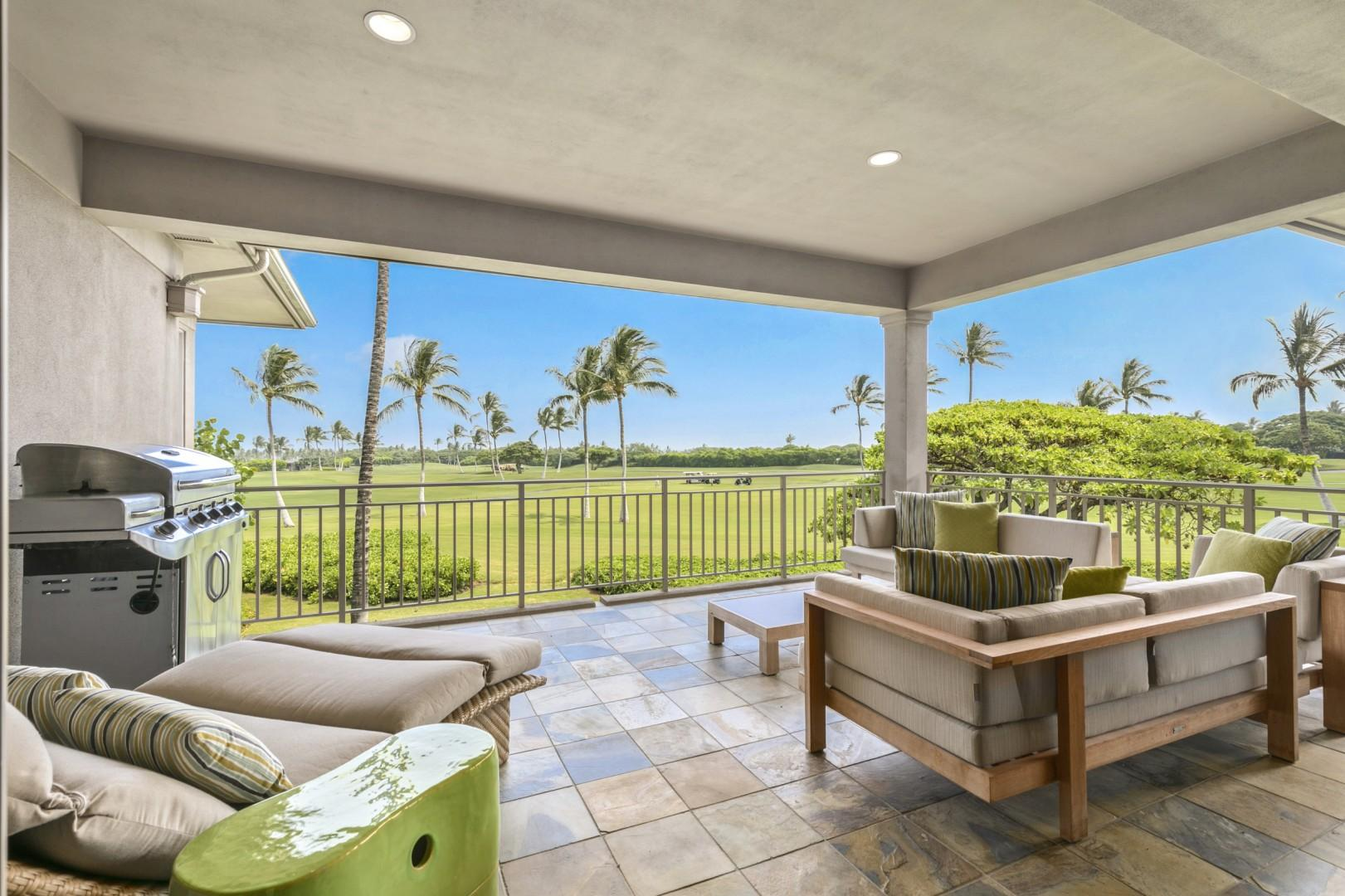 Generous Covered Lanai with Ample Seating & Views of the Hualalai Golf Course Green, Palm Trees, and Pacific Ocean Beyond.