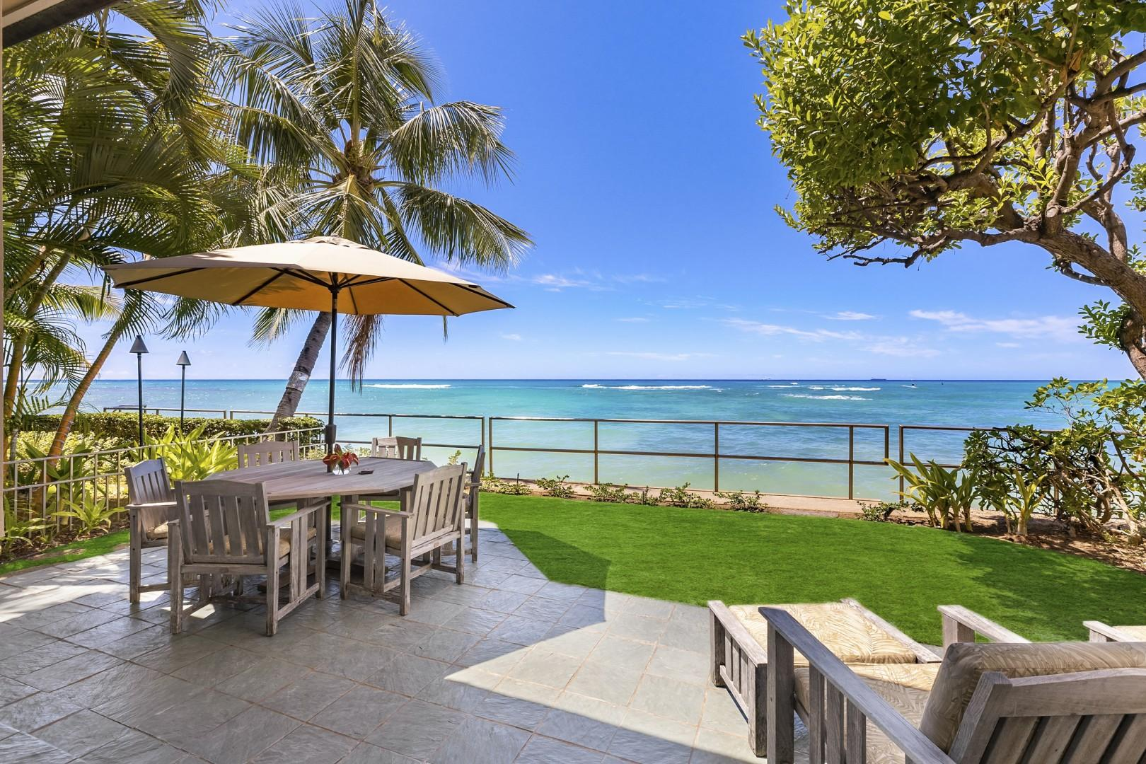 Oceanside lanai with lounge chairs and outdoor seating with umbrella.
