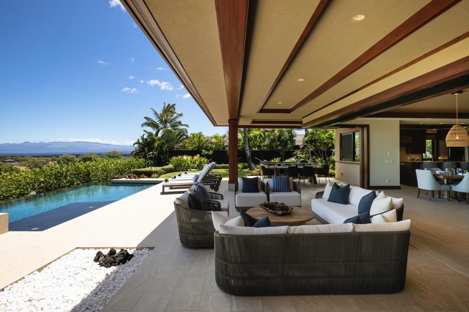 Great room transitions seamlessly onto the spacious lanai with ample lounge seating and panoramic coastline views.
