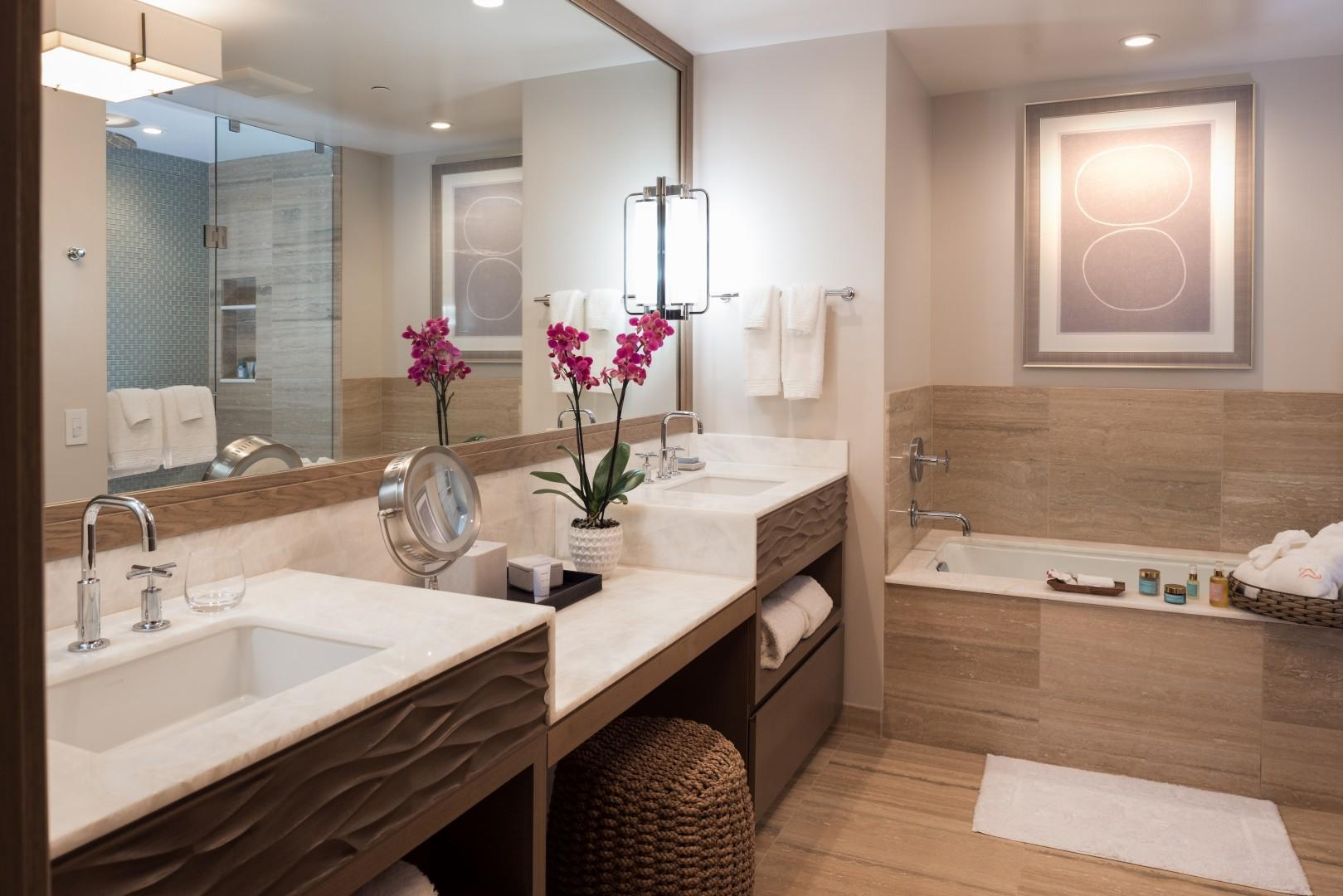A second bathroom also offers a tub, a walk-in shower, and dual sinks.