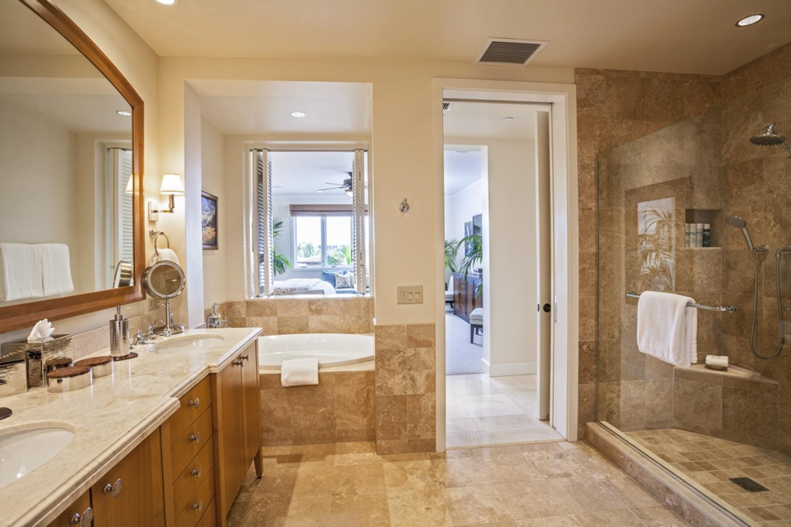 En suite master bath with deep soaking tub, glass shower, dual vanities, walk-in closet, and safe.