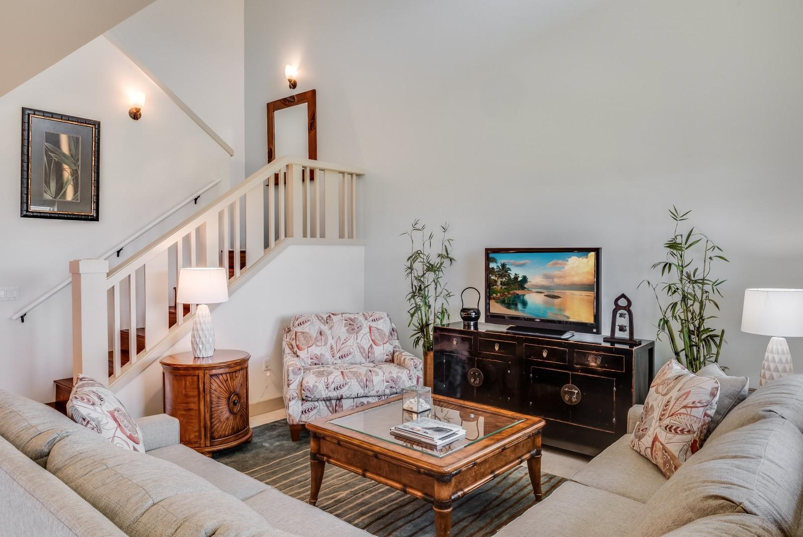 Beautiful & bright living room with two-story ceiling, staircase to second floor bedrooms