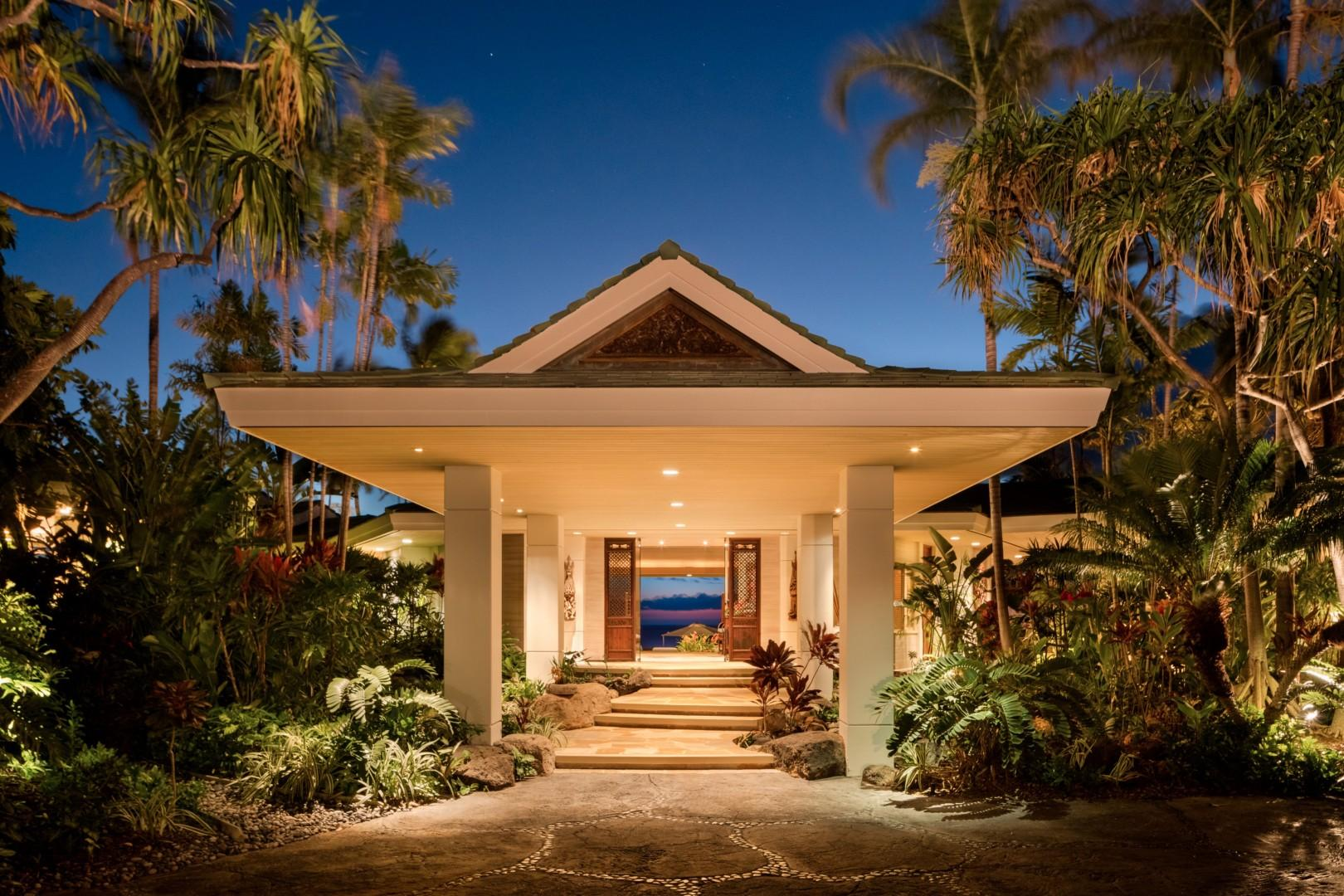 Grand entryway with tropical landscaping lit up at twilight.