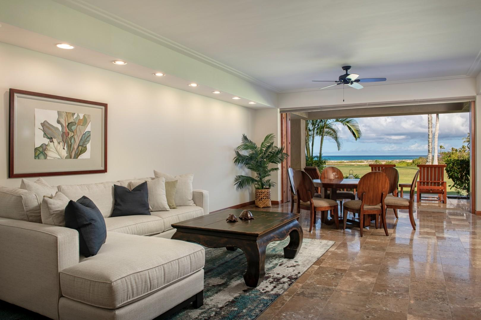 Elegant living area with sliding glass pocket doors to lanai seating and ocean views.