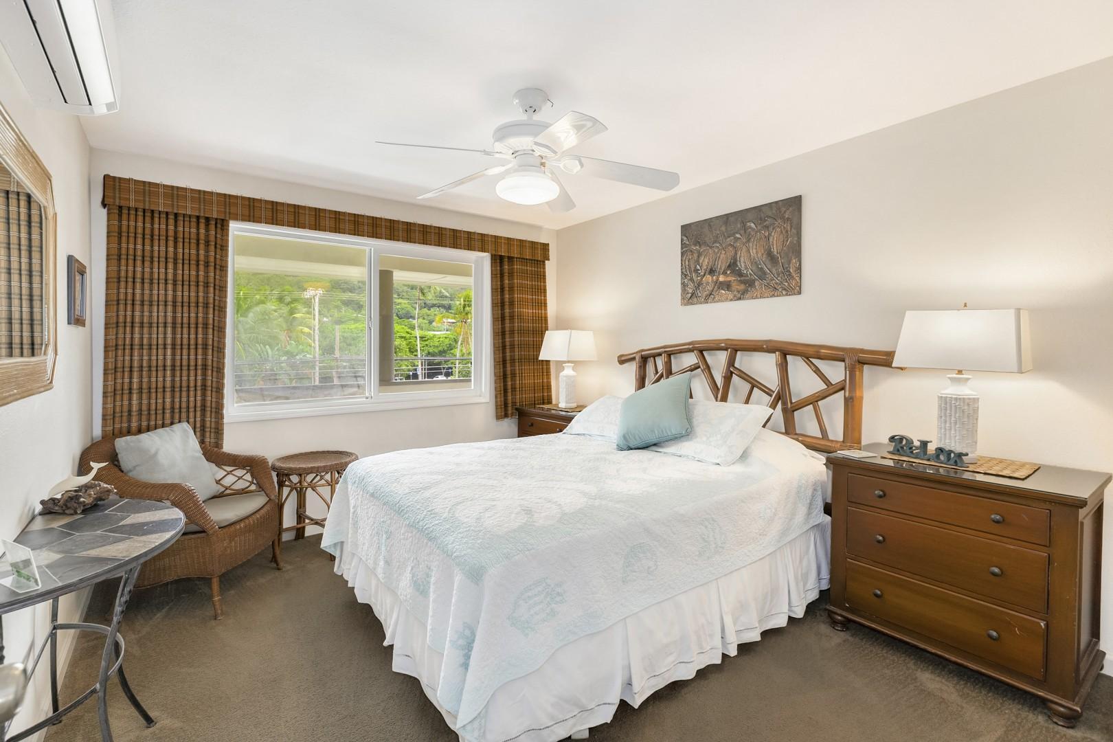 Guest bedroom with split ac, fan, dresser, and queen bed.