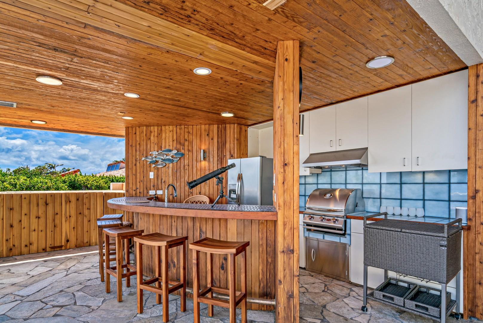 Full outdoor kitchen and bar with gas grill.