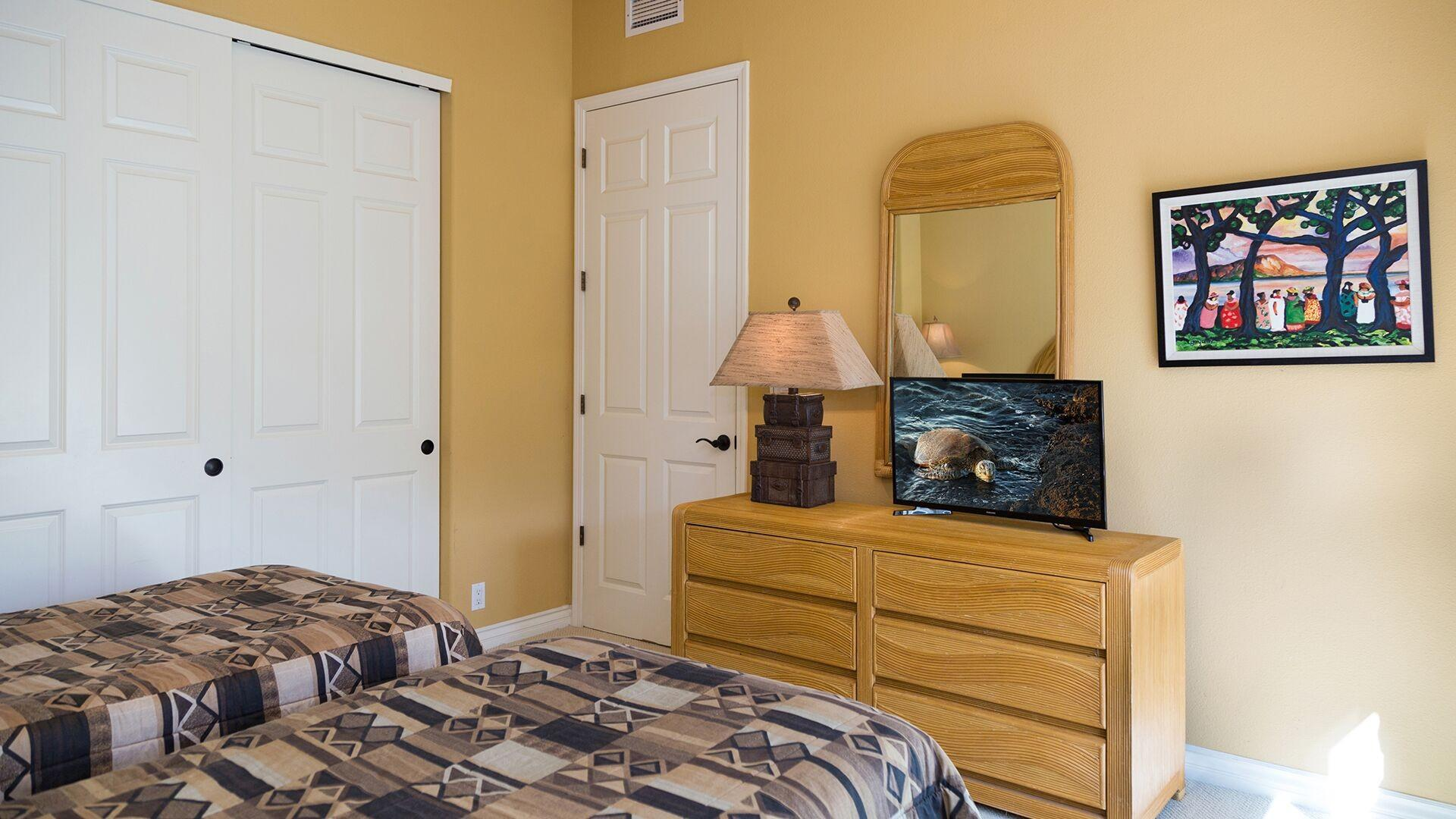 The Guest bedroom set up as twins provides a large closet and dresser with a Smart TV.