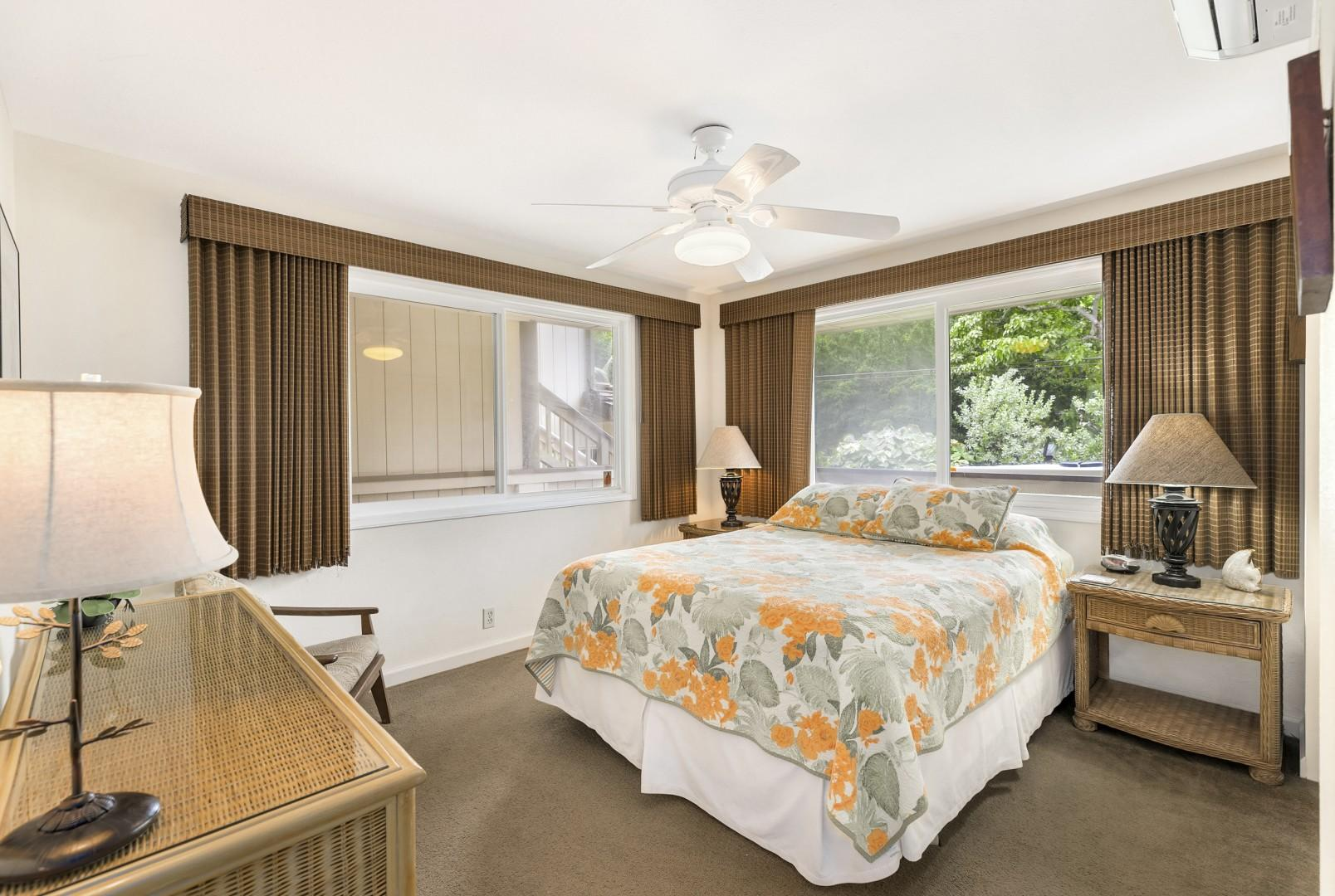 Well appointed guest bedroom with bamboo shades, dresser, split AC unit, and closet.