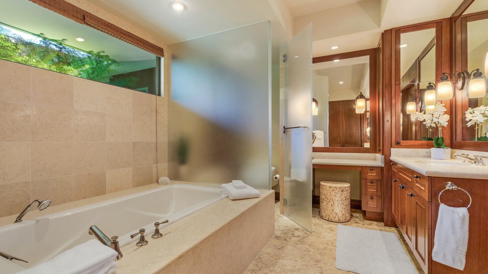 Master bath with oversized soaking tub and frosted privacy glass around the commode.