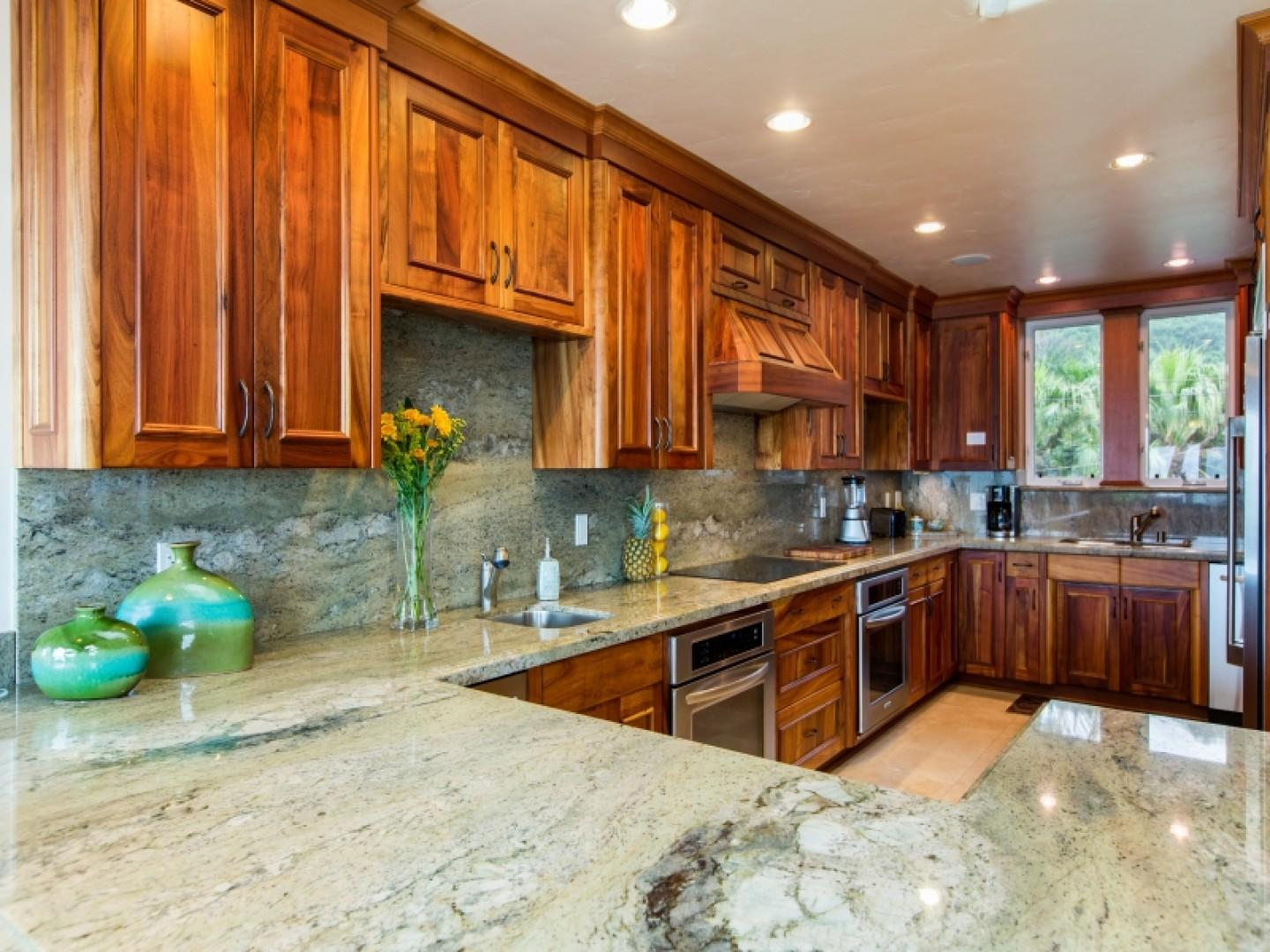 Spacious open kitchen with granite counter tops and koa wood cabinetry. Perfect for entertaining!