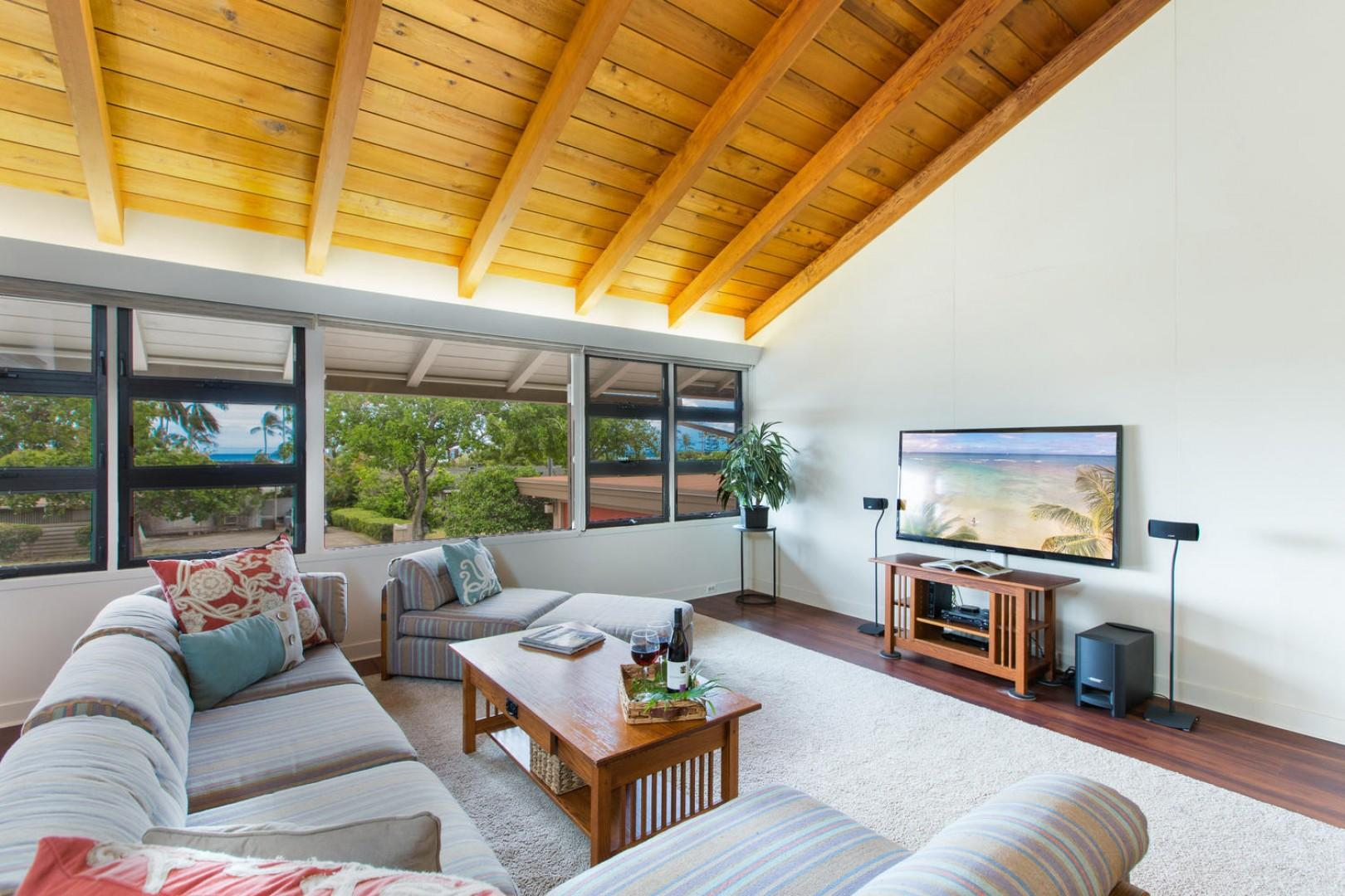 Large open-concept living room with peek-a-boo views of the ocean