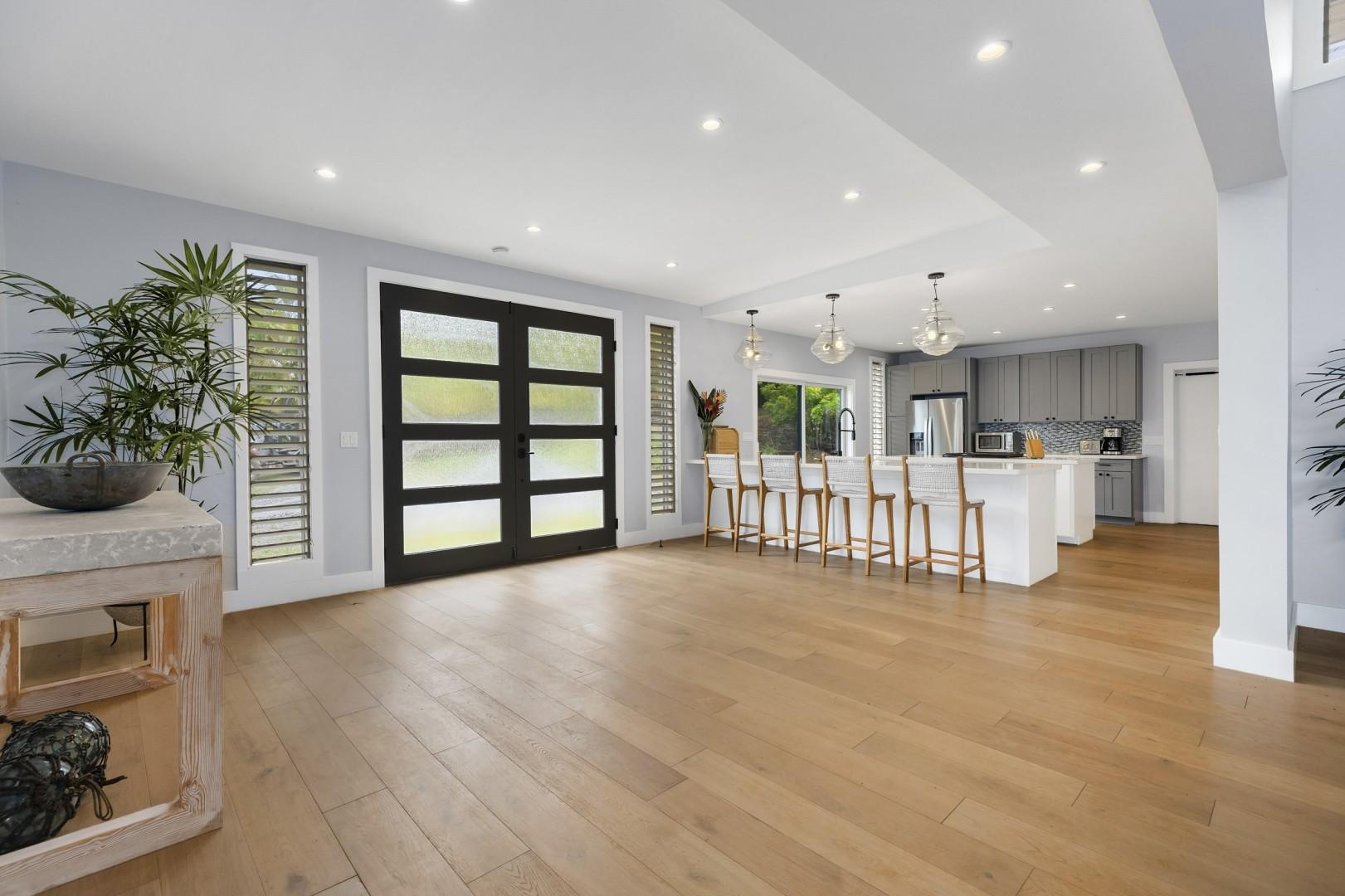Front entry doors leading into a large foyer with open kitchen.