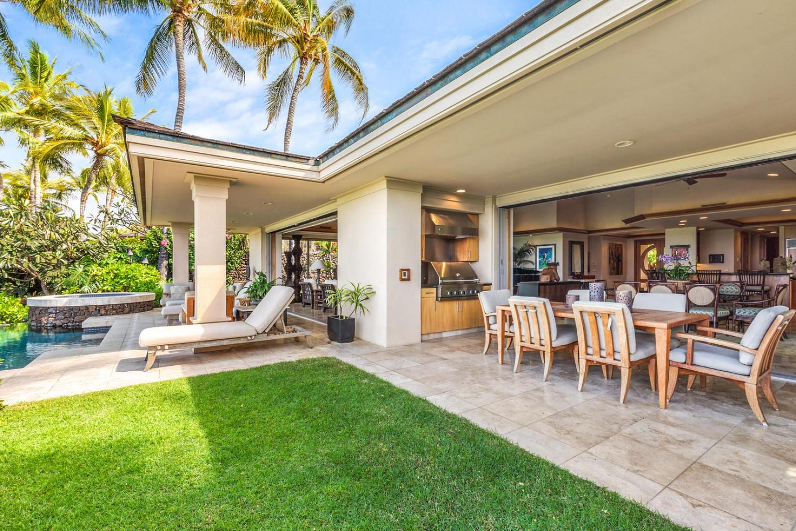 Generous lanai with private grassy yard, outdoor dining area, BBQ grill, and pool deck loungers.