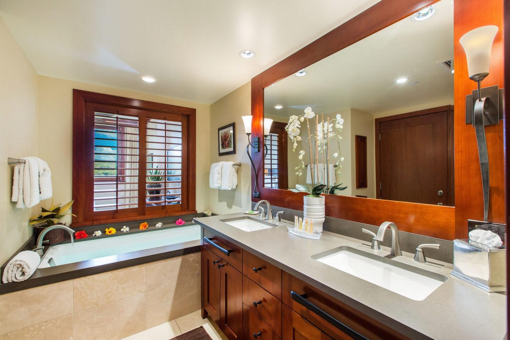Master bathroom with dual sinks, deep soaking tub, separate shower