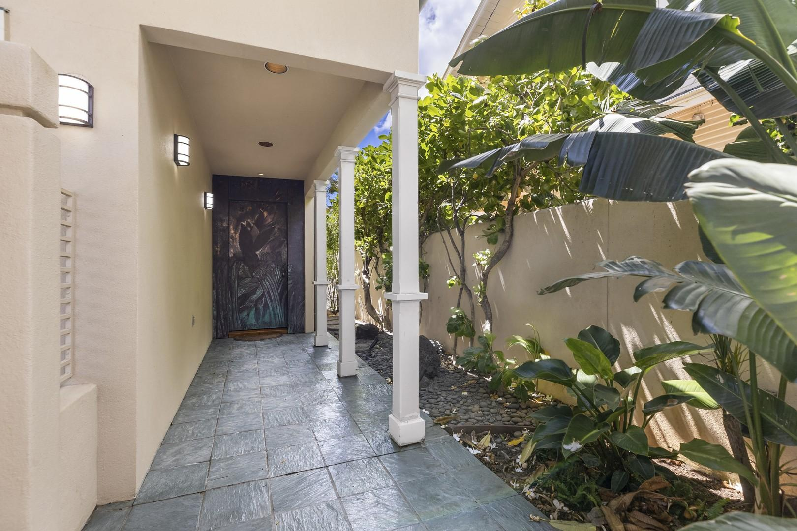 Covered walk way leads to engraved floral entry door.