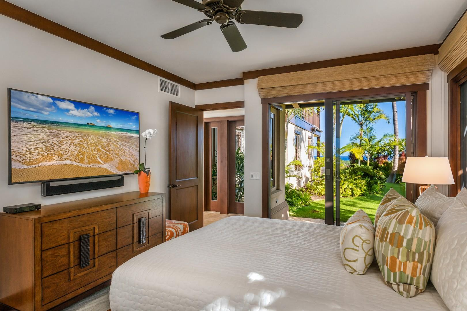 """Second bedroom with queen-sized bed, 65"""" flat-screen TV, ensuite bath and sliding doors to a private furnished lanai."""