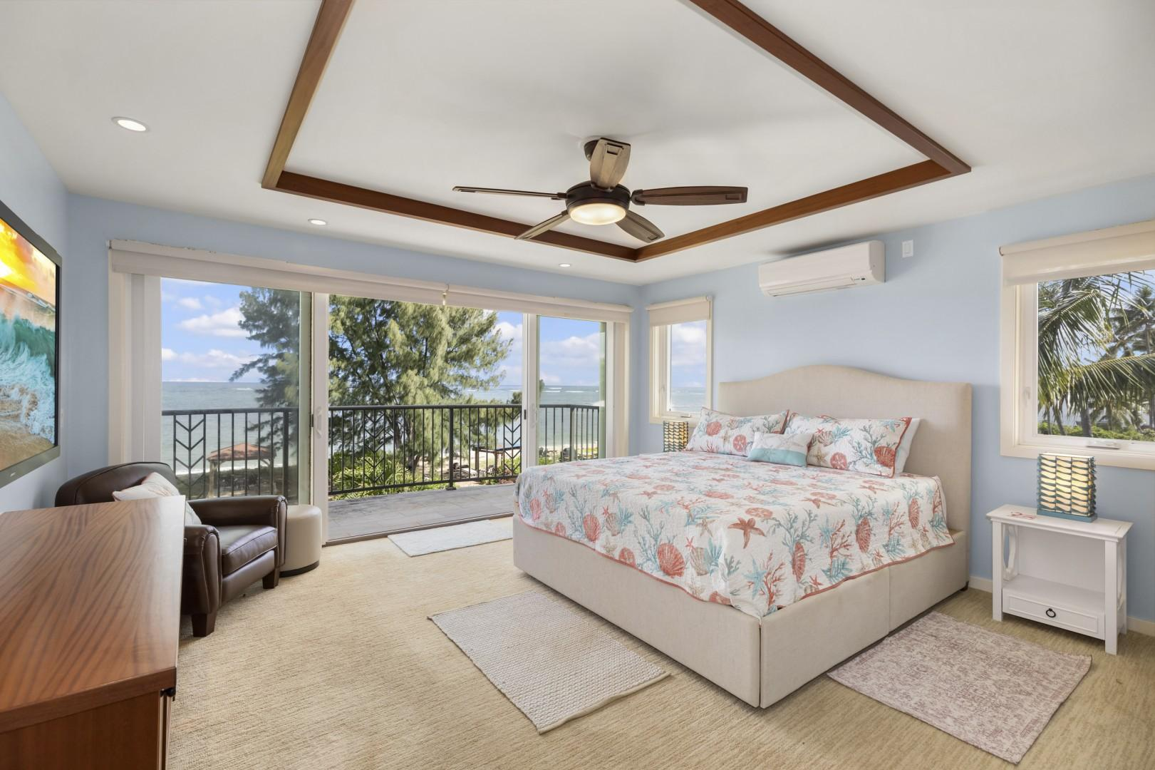 Master bedroom with Tempur-Pedic California king bed, see-through fireplace, split air conditioning, and lanai with a view of the pool and ocean.