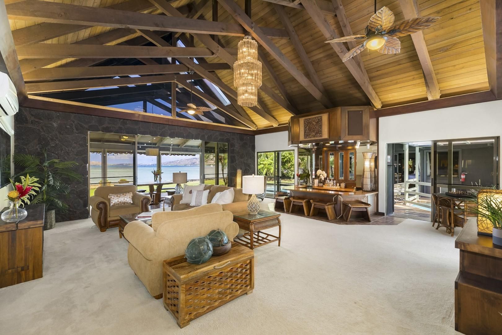 Large living room with ocean views that opens up to pool and oceanfront yard.