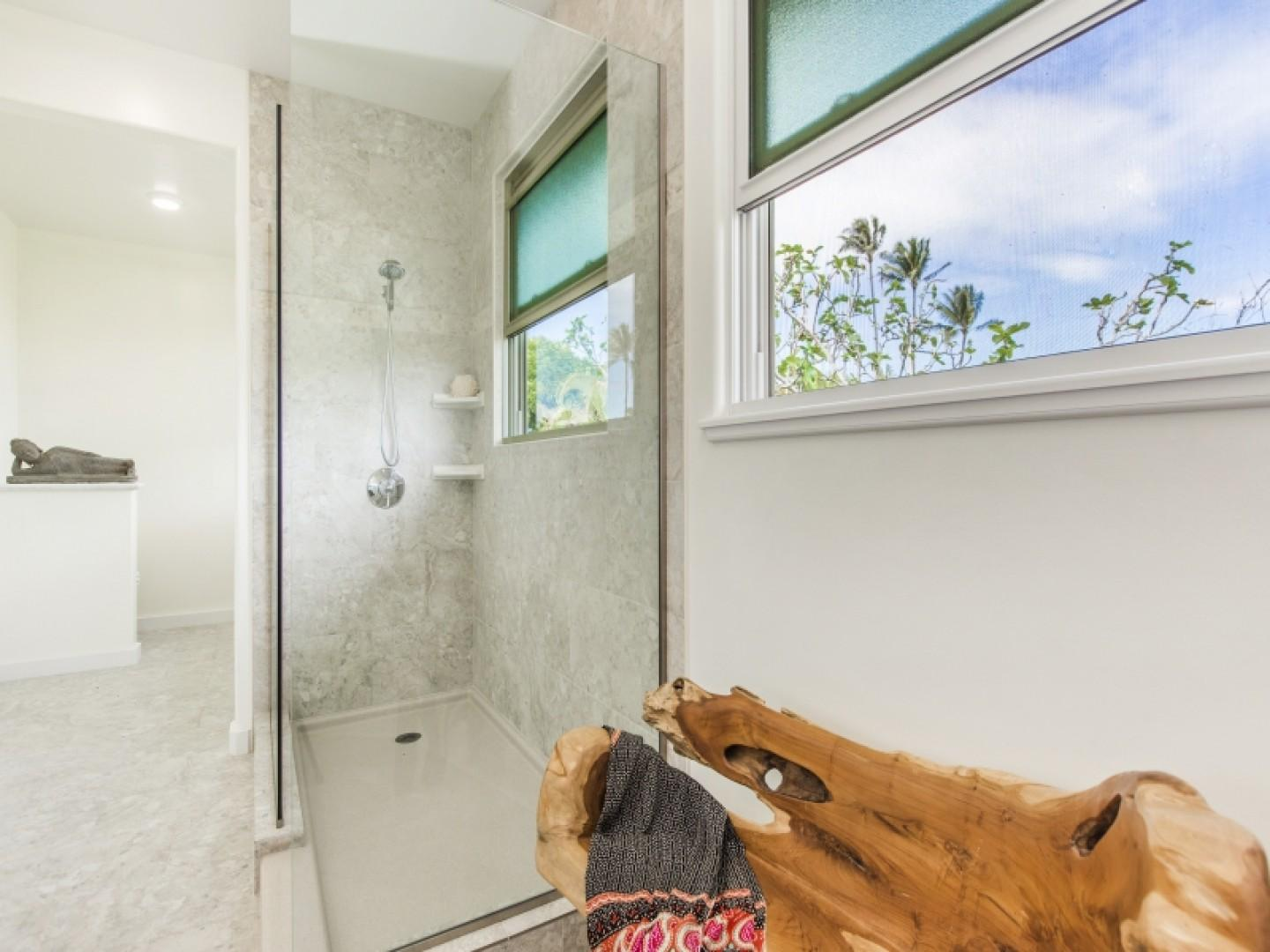 Walk-in shower with windows to take in the outdoor views.
