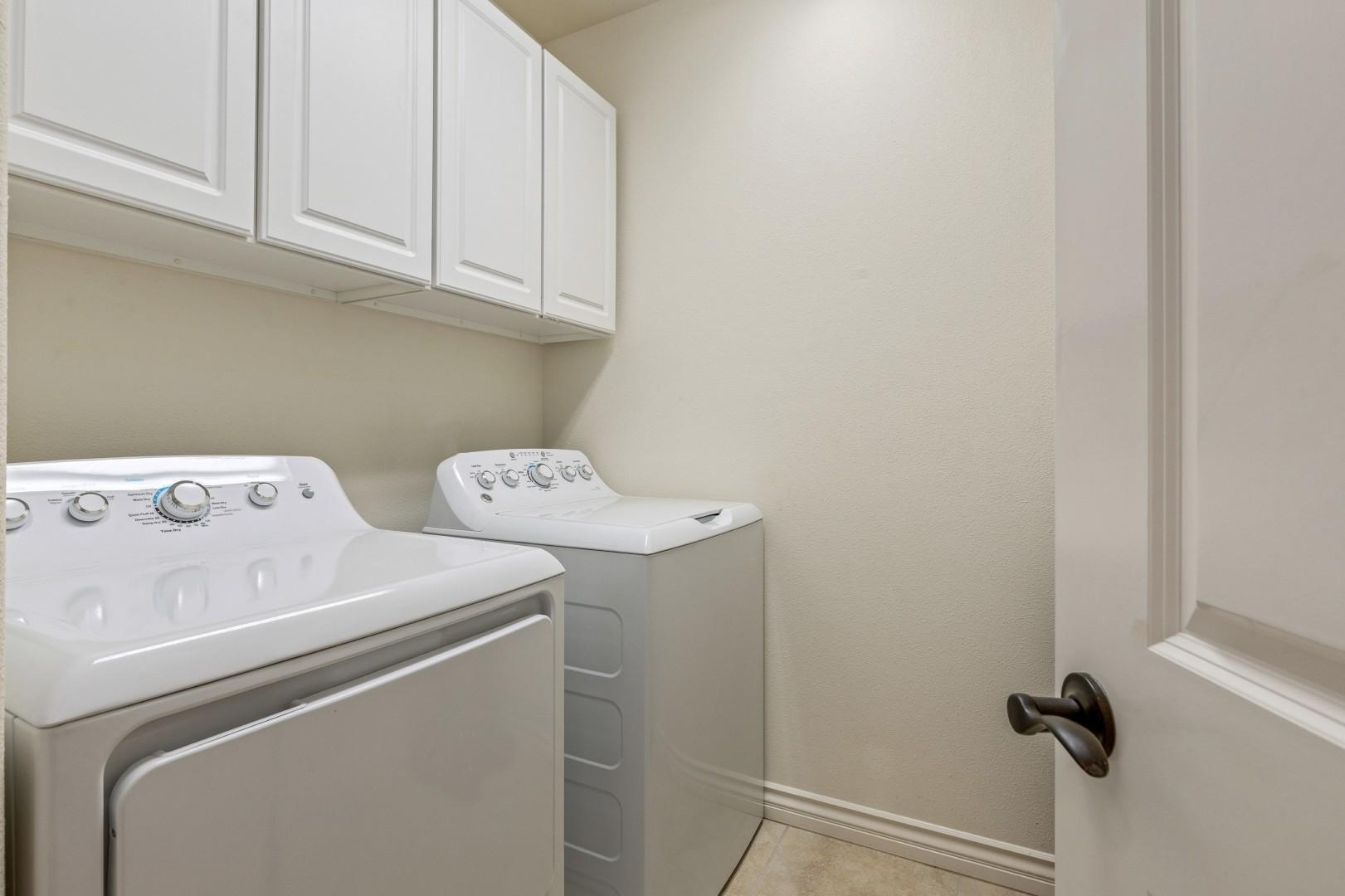 Dedicated laundry room with oversized washer and dryer and supplied laundryproducts.