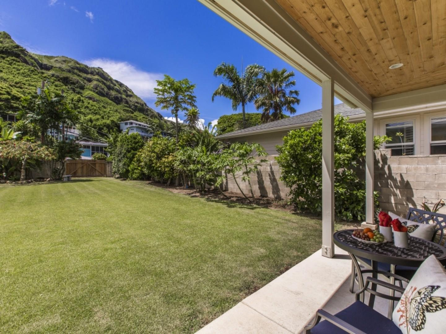 Covered lanai allows guests to enjoy the beautiful outdoor lawn area.