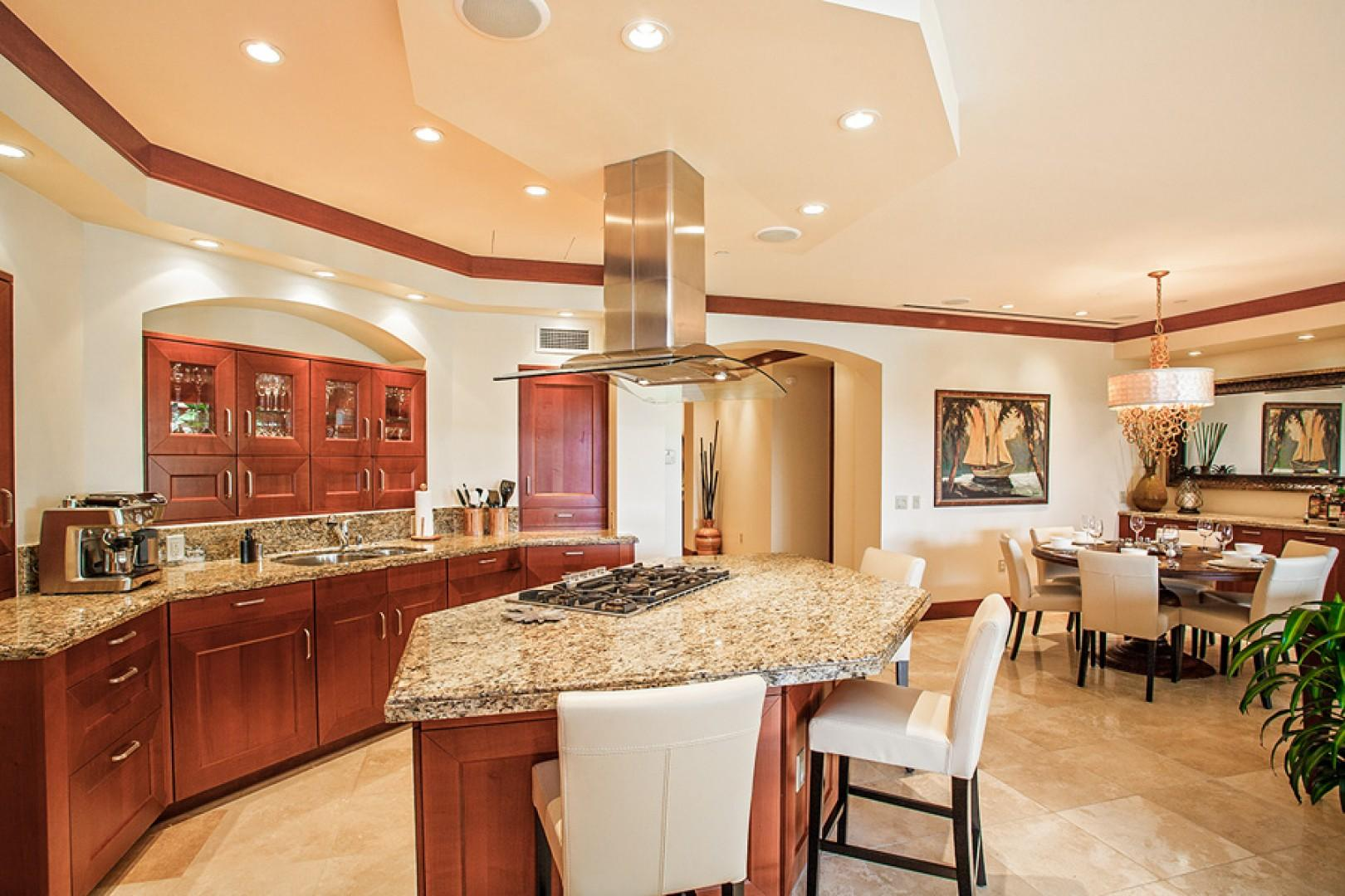 Gourmet kitchen with bar seating and formal dining space beyond.