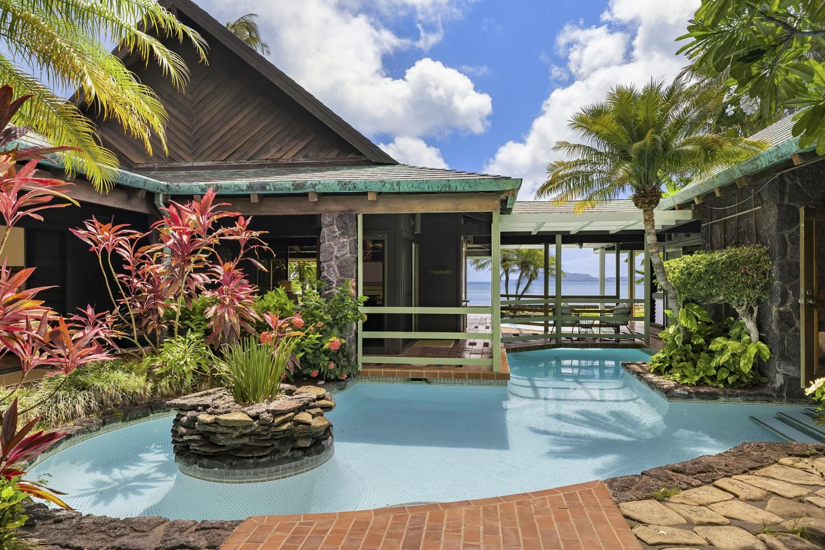 Large resort-style pool meanders through courtyard towards oceanfront lawn.