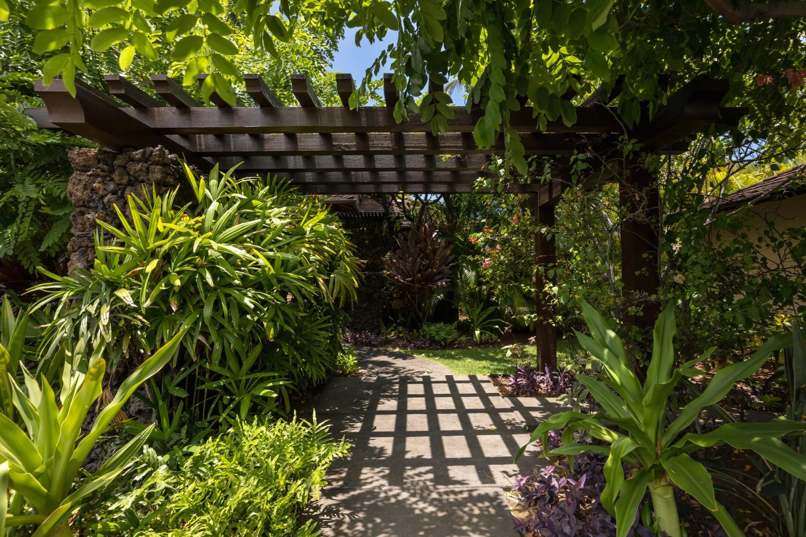 Exterior entryway leading to front door with lush tropical landscaping.