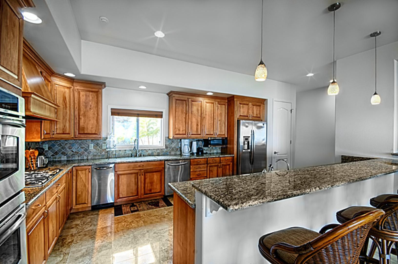 Large, open, fully equipped kitchen with bar stool seating.
