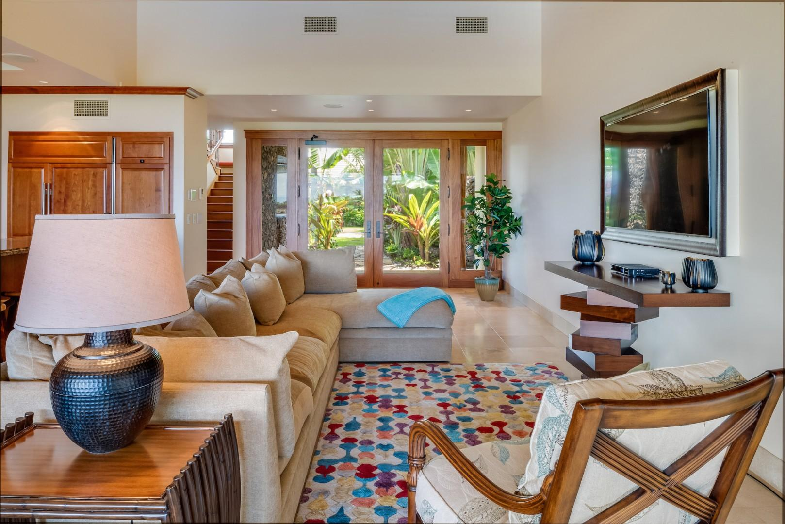 Double Doors from Courtyard Enter into Living Room w/ Plush Sofa and Large Flatscreen TV.