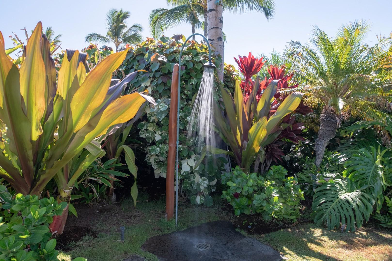 Outdoor shower by the pool surrounded by colorful tropical foliage