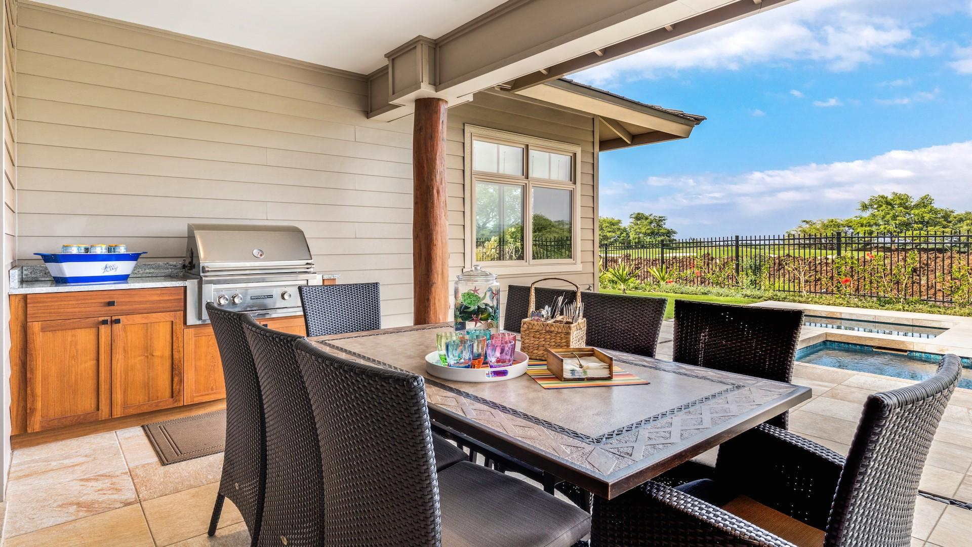 Outdoor dining set for eight with view of built-in barbecue grill.