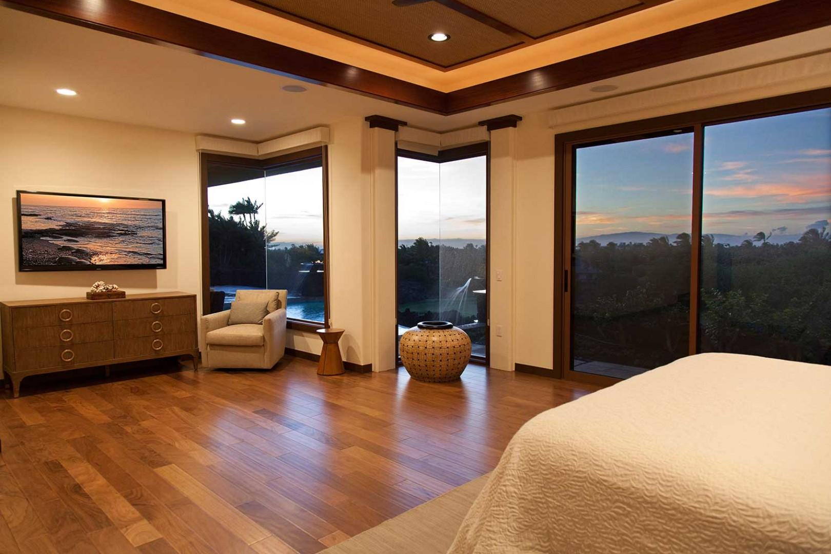 Master bedroom with sunset and ocean views, king bed, hardwood floors, and mounted flat-screen TV.