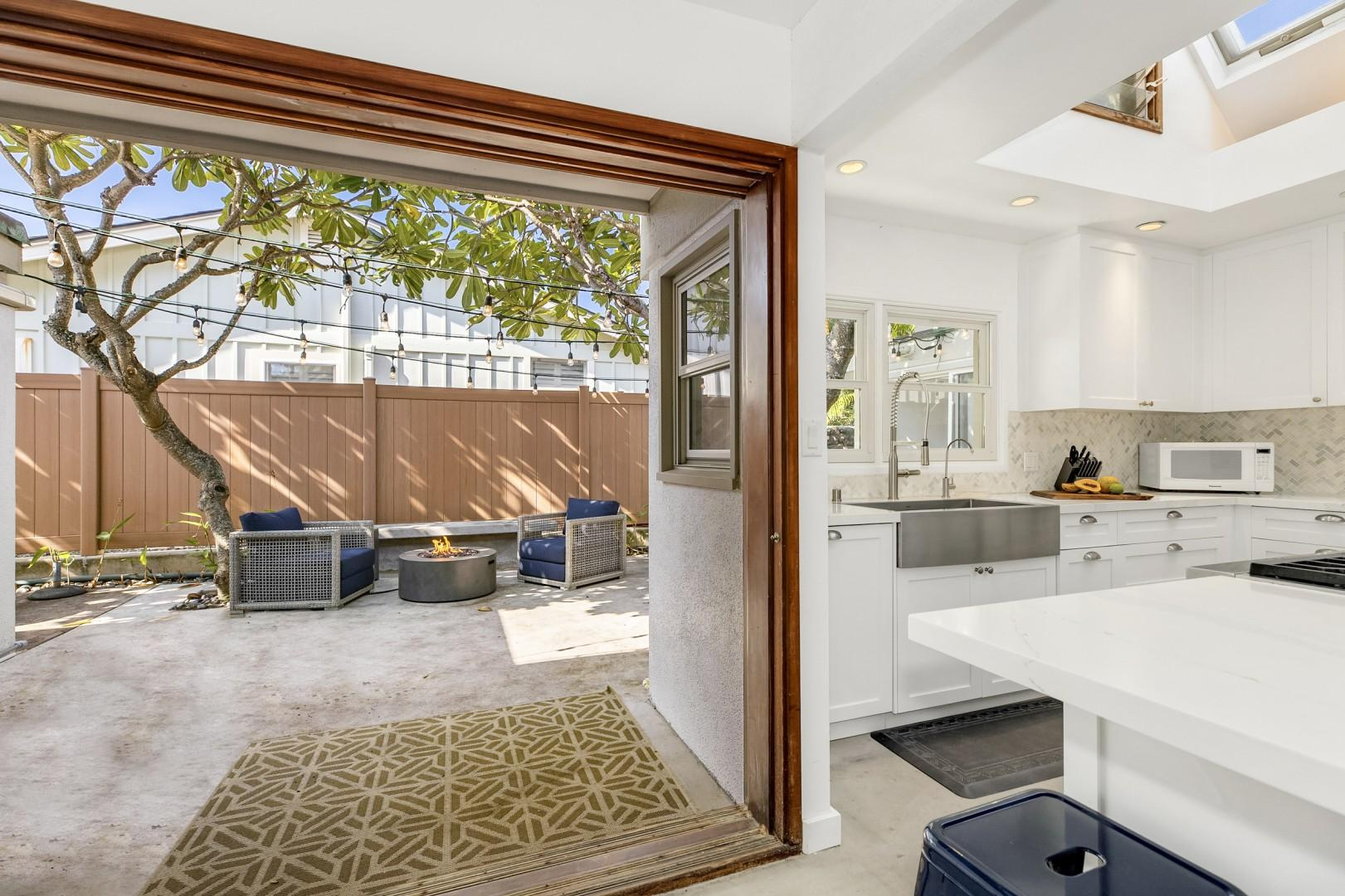 Kitchen with views of the plumeria lanai, where you can relax and BBQ!
