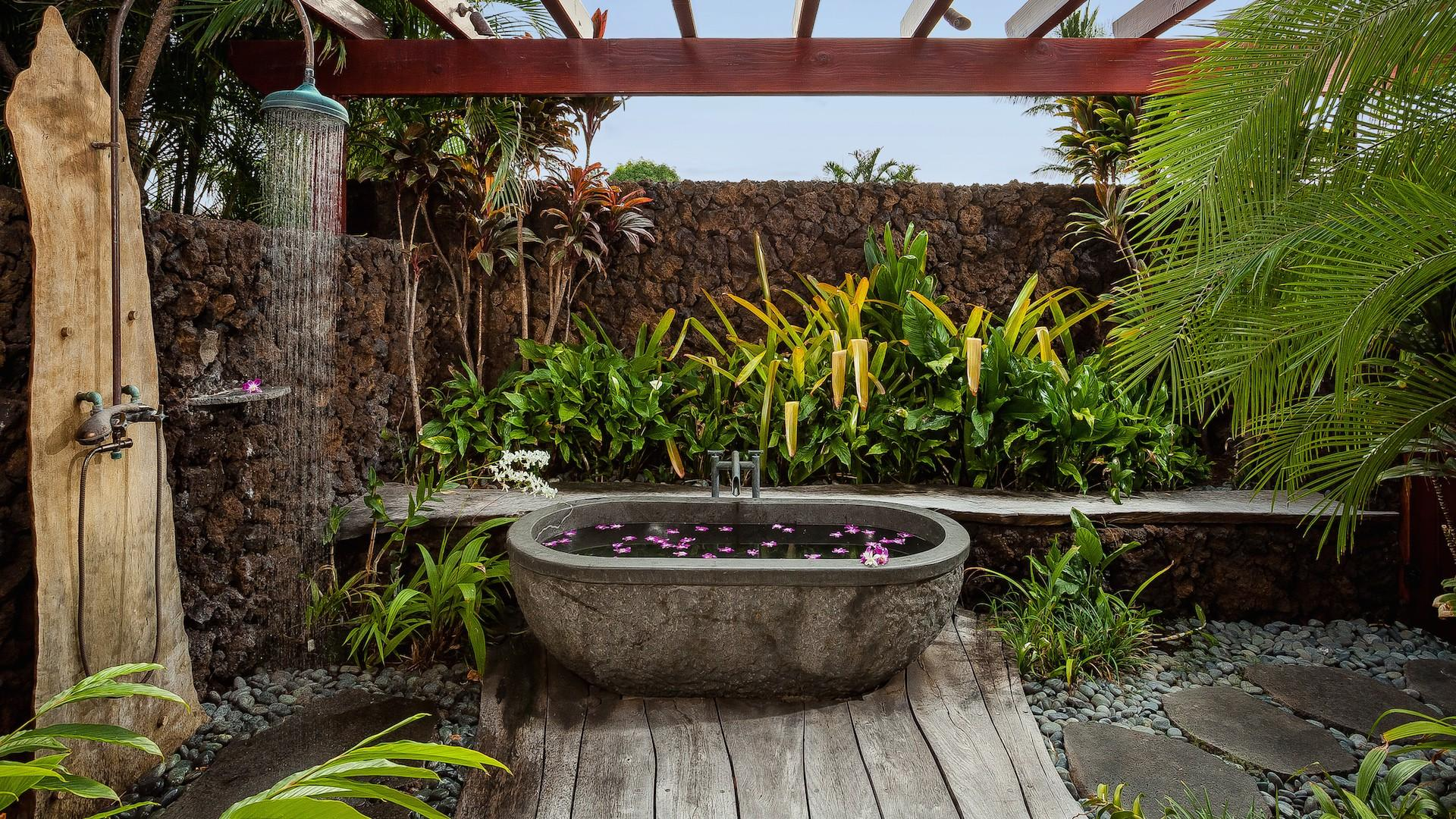 Outdoor shower garden and cast stone soaking tub surrounded by tropical landscaping.
