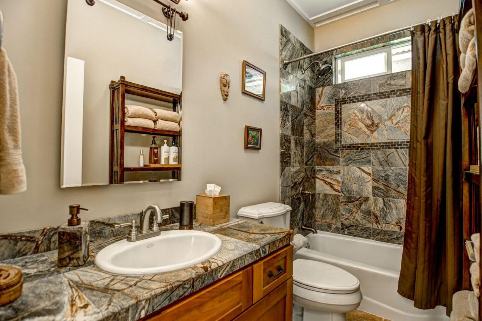 Bathroom 3 is shared with two bedrooms and has a full tub with shower and elegant marble tile