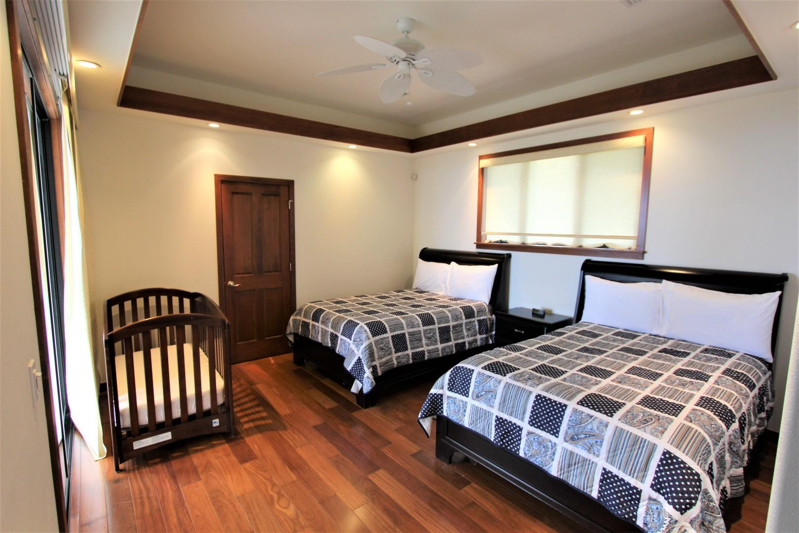 Guest bedroom equipped with two Double beds and crib