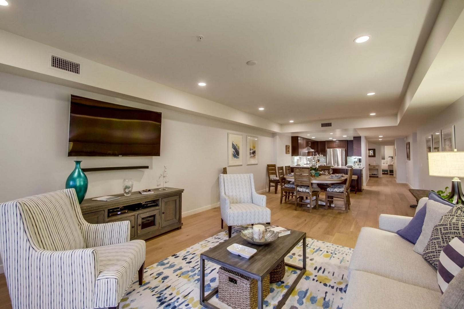The living room features a flat screen and soffit ceiling with recessed lighting