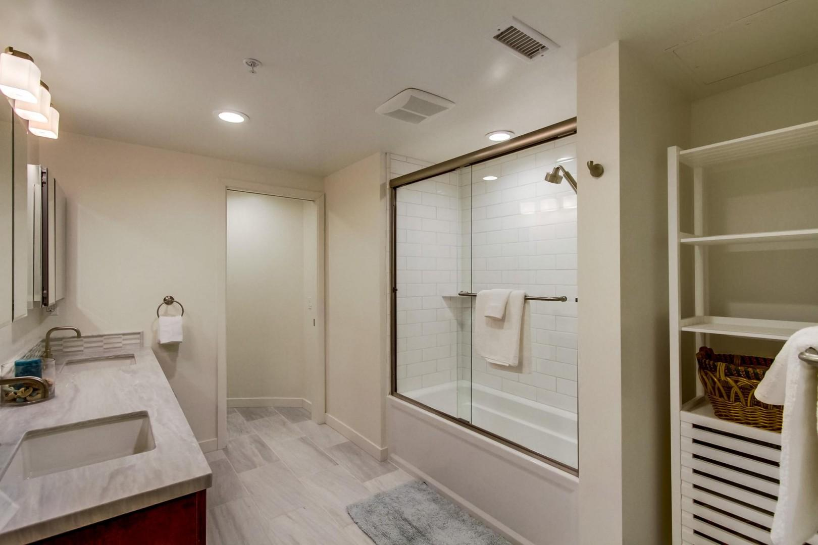 Hall bath adjacent to bedroom 2 features a dual-sink vanity and tub-shower combo