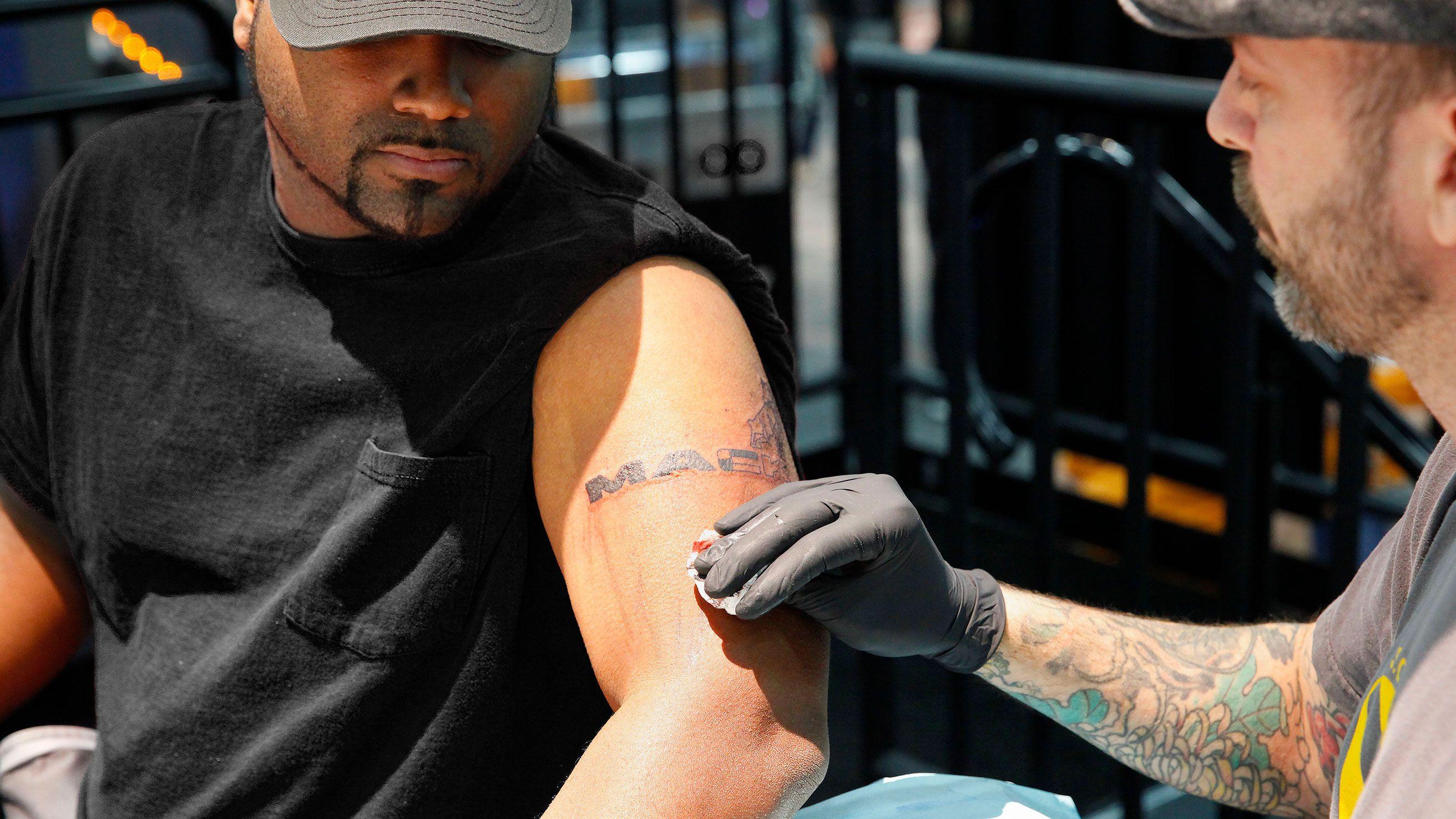 Person getting a Mack Trucks tattoo
