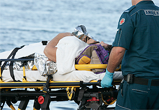 Image of injured boater on a gurney by the water