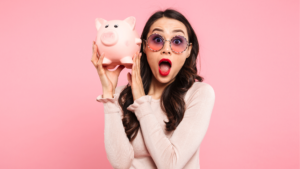 a woman excitedly holds up a piggy bank