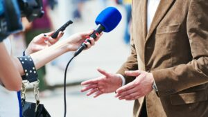 a woman filming an interview video with a blue microphone