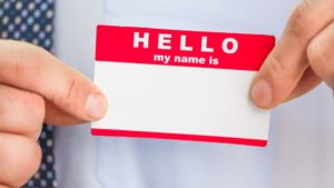 "man holding ""Hello my name is"" name tag sticker demonstrates an element that could have a viewer's name on it in a personalized video"
