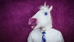 businessman wearing a plastic unicorn mask
