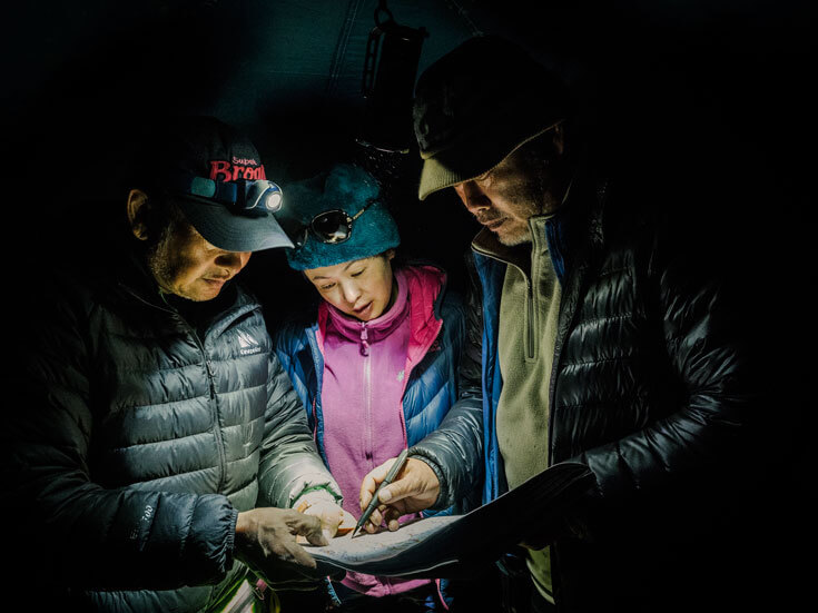 A woman stands between two men, wearing jackets and hats and standing in darkness as they consult a map.